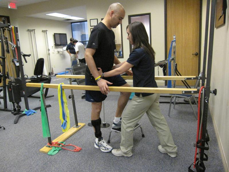 Physical therapist helping patient walk